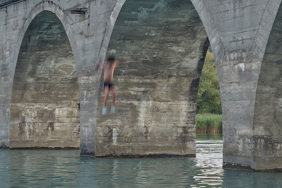 The image shows the photograph of a boy jumping from a bridge into the water of the Wohlensee (Lake Wohlen).