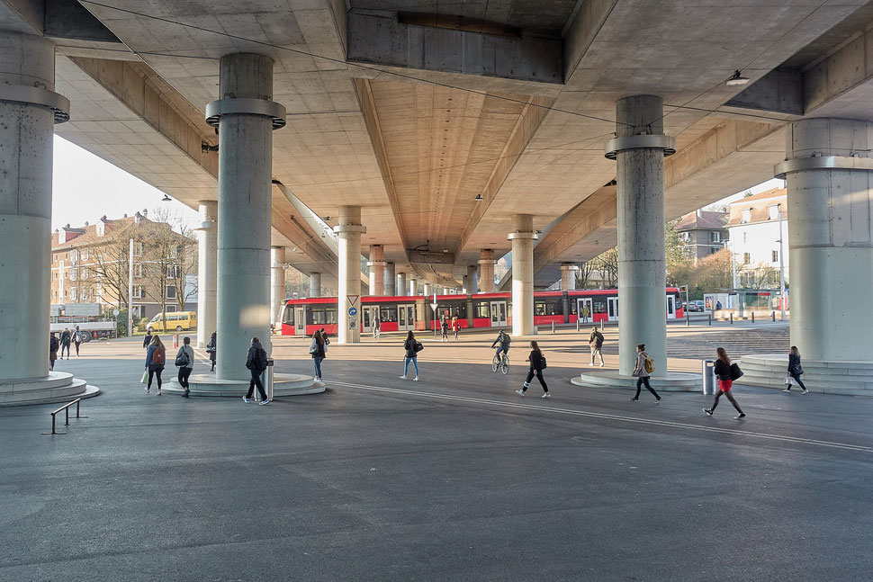 The image shows the photograph of Europaplatz Bern with some people crossing the square, a stopped red tram and a huge concrete overpass.