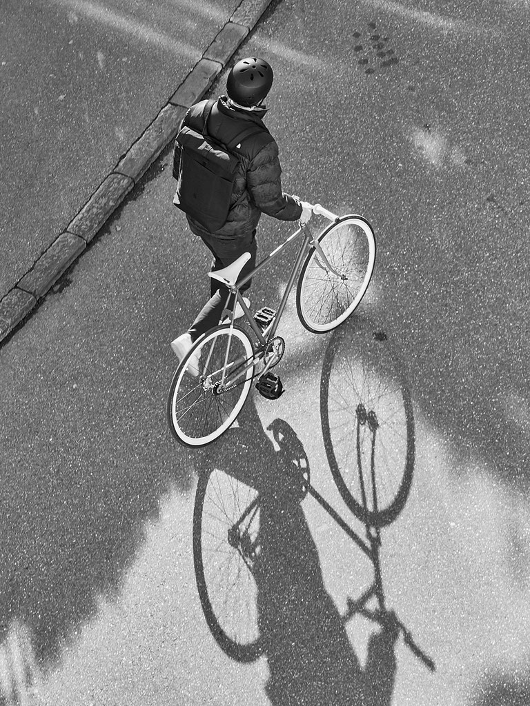 The image shows a bird's eye view of a man pushing his bike up a steep hill; the bike throws a shadow on the ground. The photograph is black and white.