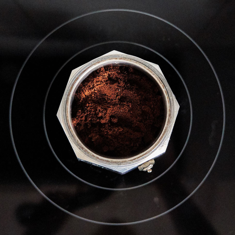 The image shows the photograph of an open Italian coffee maker with sunlight on ground coffee, which is placed on a cooking plate.