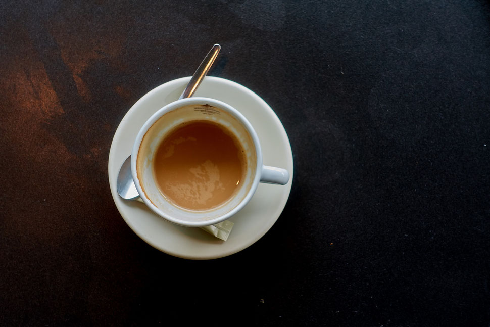 The image shows the aerial photo of a white cup of coffee on a dark table.