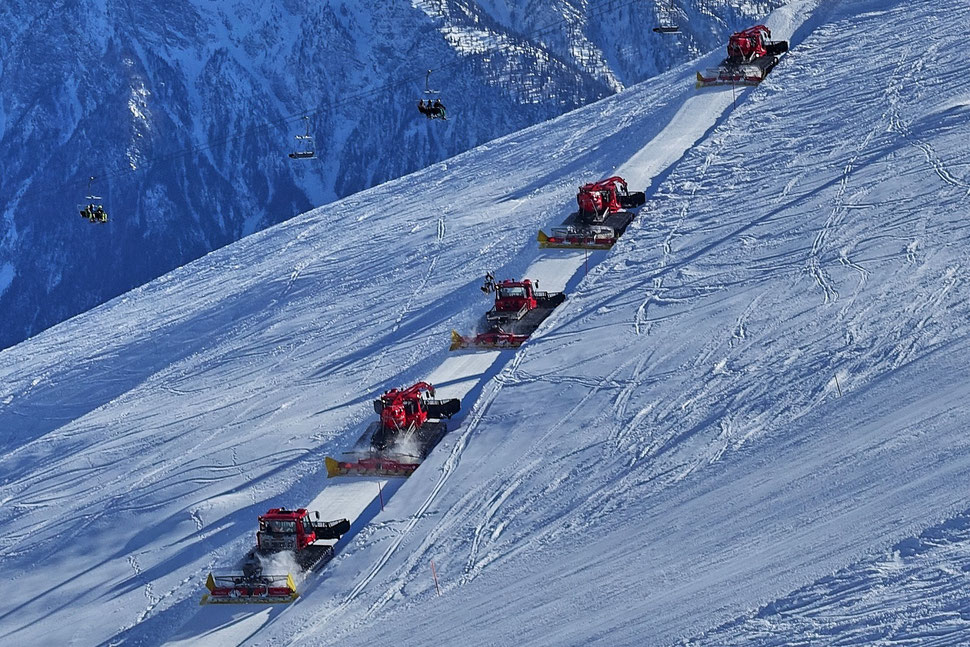 The image shows the photograph of five snow groomers crossing a ski slope against the background of mountains.