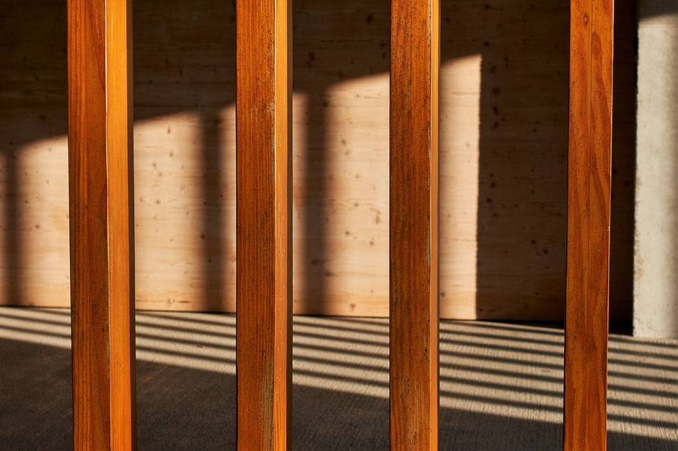 The image shows several wooden beams that are light by late afternoon sunshine and produce a pattern on the floor of a pavillion.