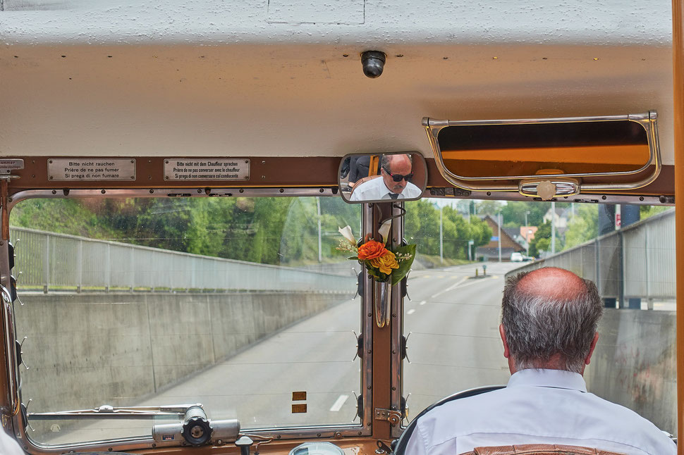 The image shows the photograph of the back of the head of a bus driver and the windshield with the road ahead. You can see the driver's face in the rear view mirror, which is placed in the center above the windshield.