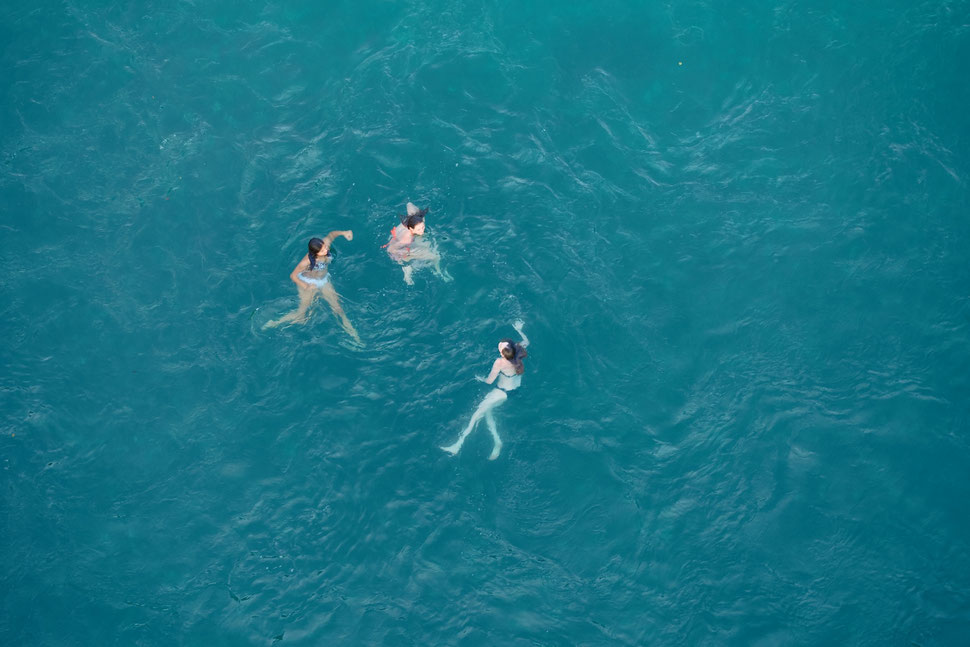 The image shows the aerial view of three girls swimming in a river.