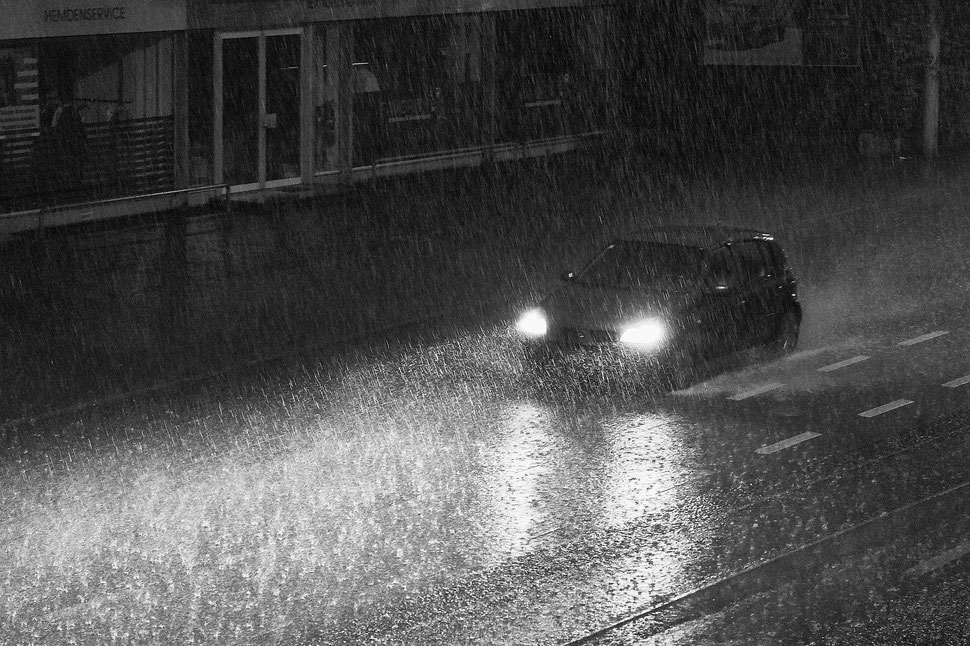 The image shows the photograph of a car driving through a heavy rainstorm its headlight lighting the street and the raindrops.