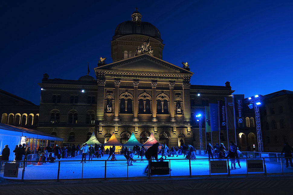 The photograph shows an atmospheric image of people skating on an ice skating rink in front of the federal palace in Bern.