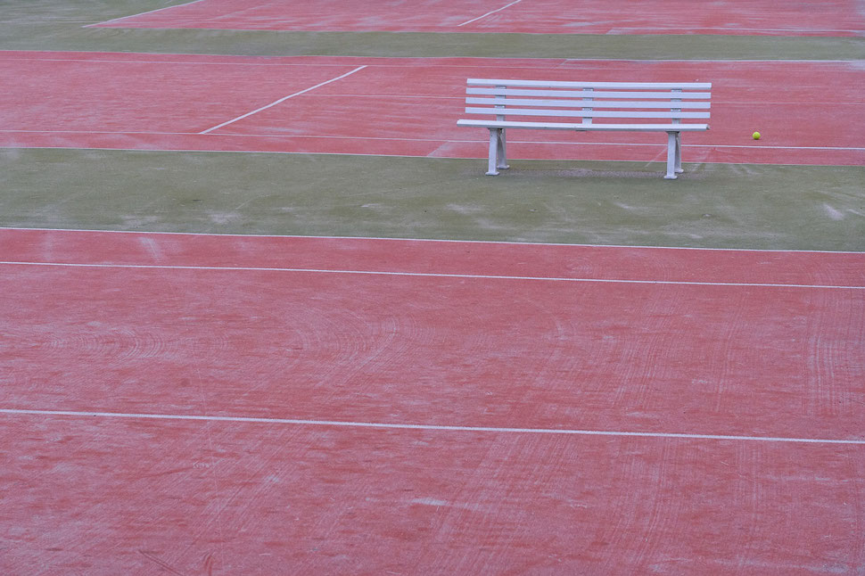The image shows the photograph of vacant tennis courts an a white bench and a single tennis ball. It is early morning.
