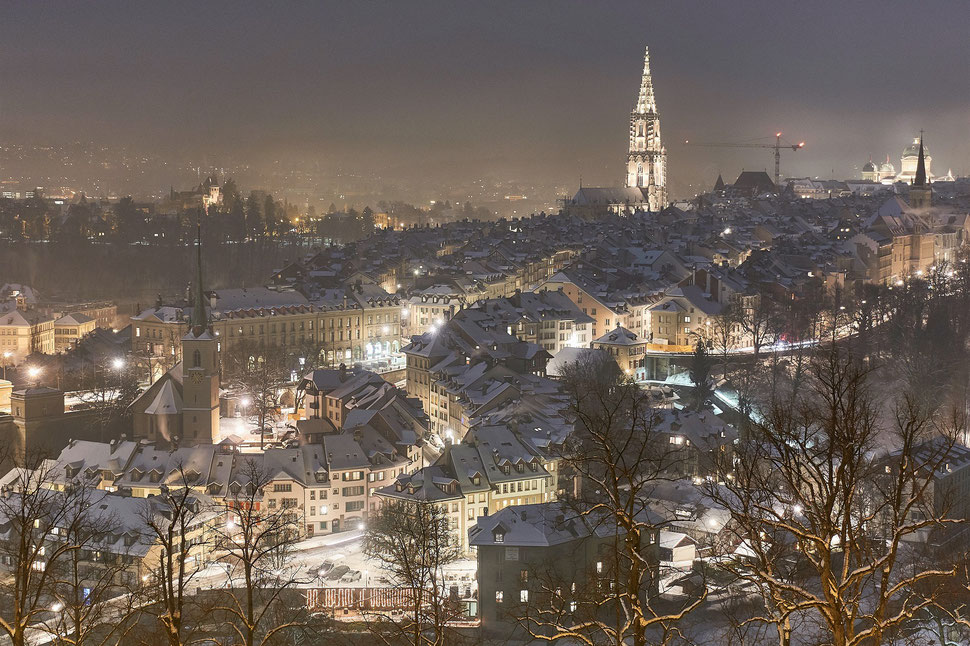The image shows the nocturnal photograph of the city of Bern in Winter. The roofs are covered with snow and the streetlights light the city.