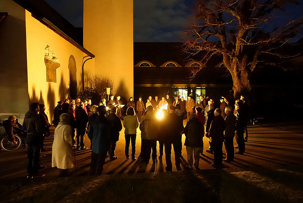 The image shows a night photograph of people gathering around a fire in front of the protestant church in Bümpliz.