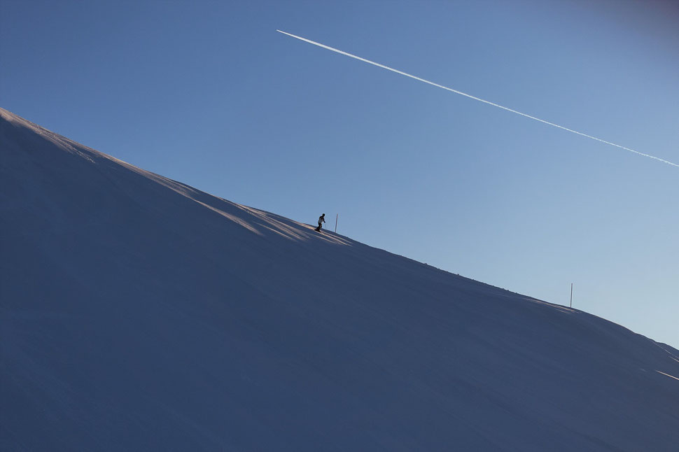 The image shows the photograph of a single skier on an empty slope and under a blue cloudless sky.