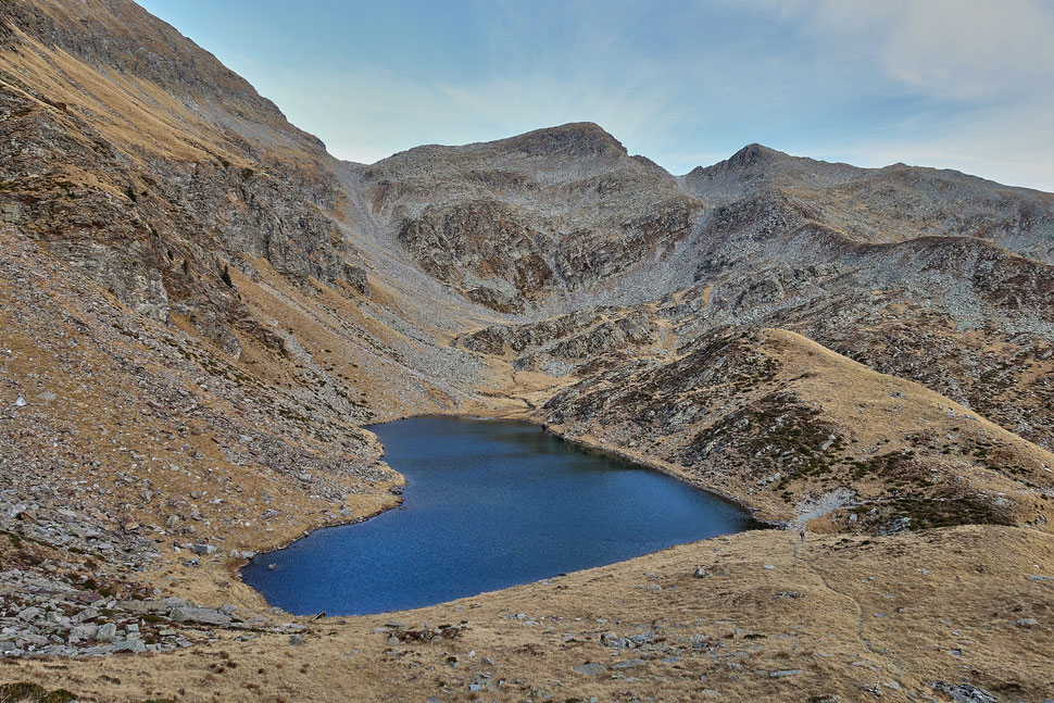 The image shows the photograph of a heart shaped mountain lake in a rugged mountain environment.