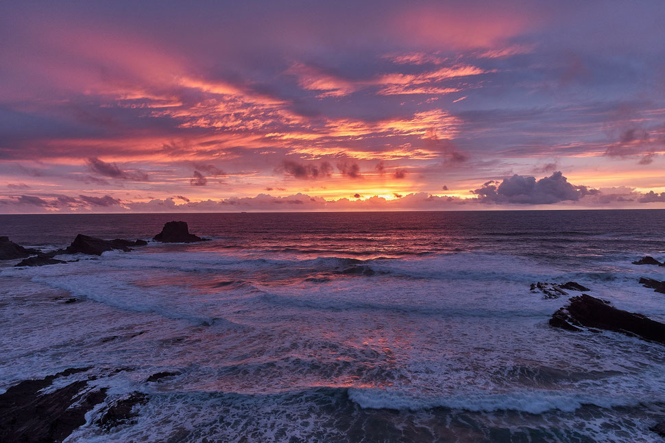 The image shows a spectacular sunset over the atlantic ocean with lots of red, yellow, pink and blue shades.