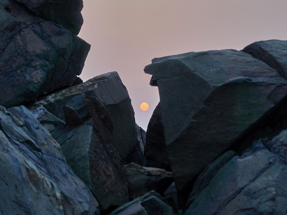 The image shows the photograph of the rising sun in a gap of dark rocks.