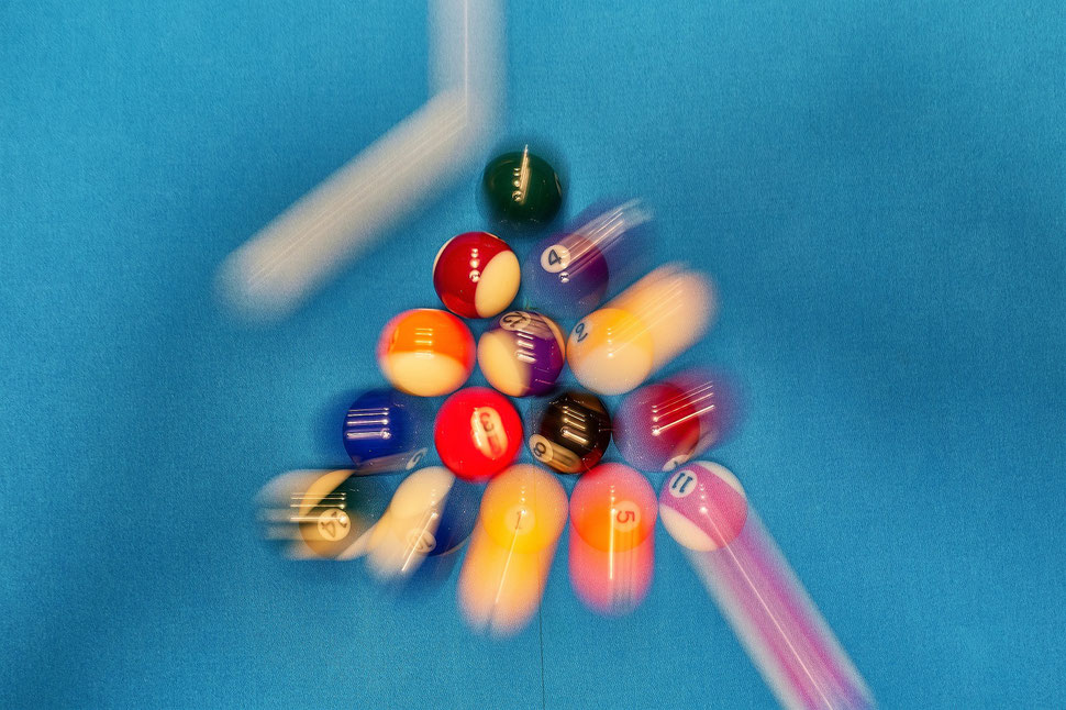 The image shows the aerial photograph of a full set of billiard balls that are hit by the white ball during the break shot.