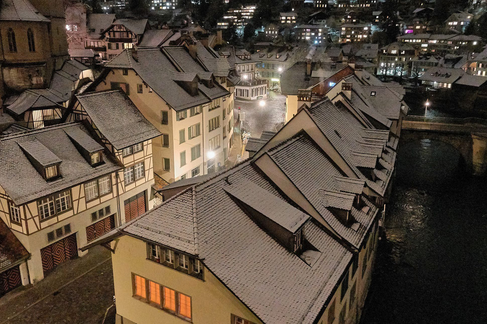 The image shows the nocturnal photograph of snow covered houses of Bern's old town. The houses are lit by steet lights.