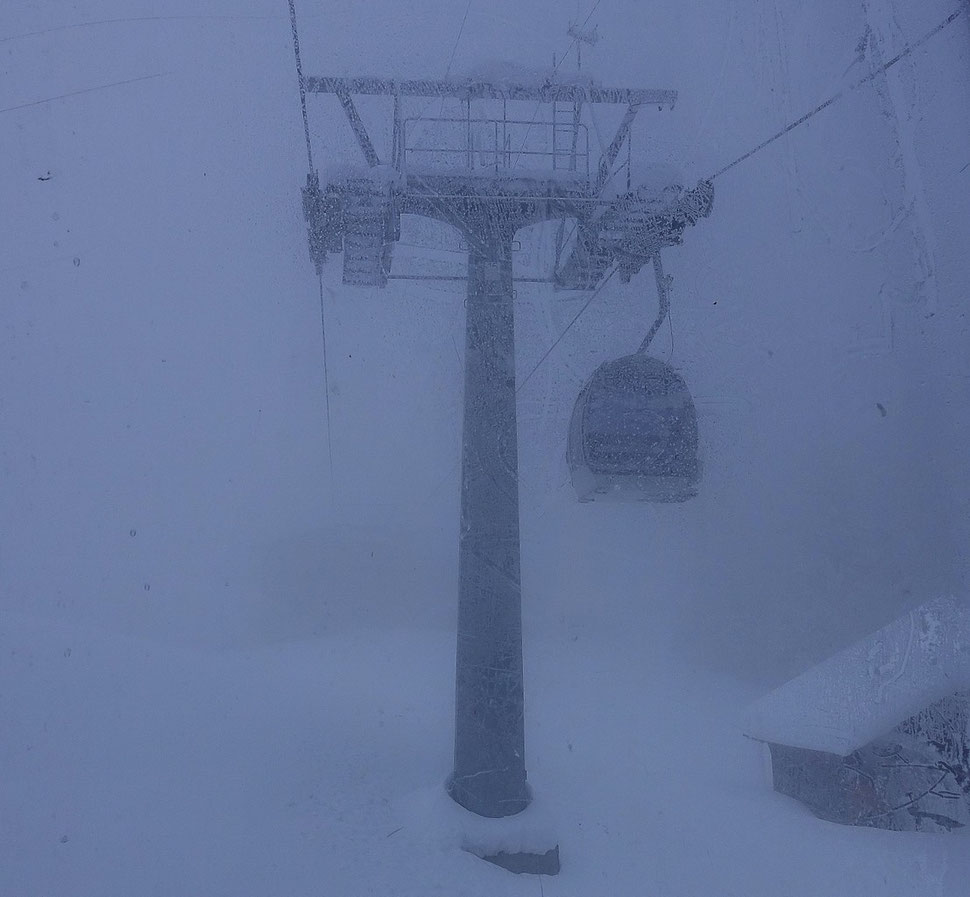 The photograph shows an image of a gondola that is crossing a mast  in a surrounding of thick fog an snow.