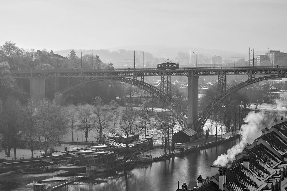 The image shows the black and white photograph of a vintag tram crossing the Kirchenfeldbrücke in Bern.