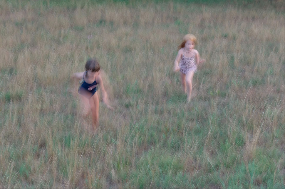 The image shows a blurry photograph of two little girls running through a field of grass.
