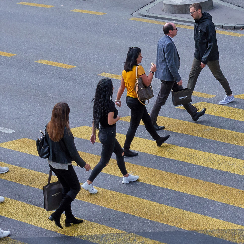 The image shows an photograph of five people crossing a road on a yellow crosswalk.