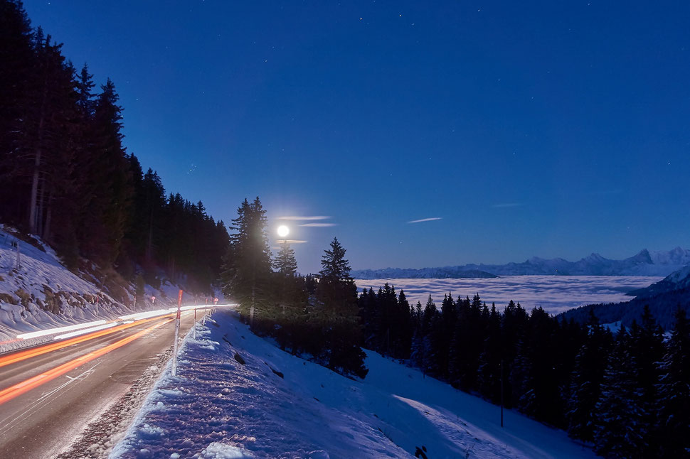 The image shows a photograph of a winterlandscape with mountains, fir trees and a full moon rising over the horizon. There's a road in the left part of the image with light tracks of cars that passed.
