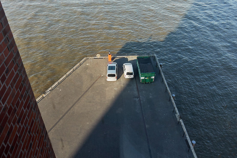 The image shows an aerial photograph of two parked cars next to a large green container.
