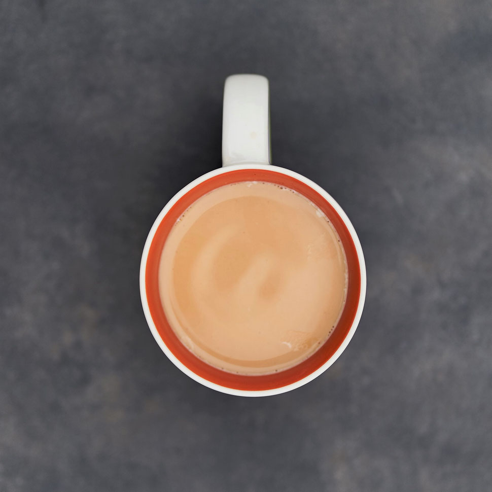 The image shows a a bird's eye view of a cup of coffee standing on the dark grey surface of a table.