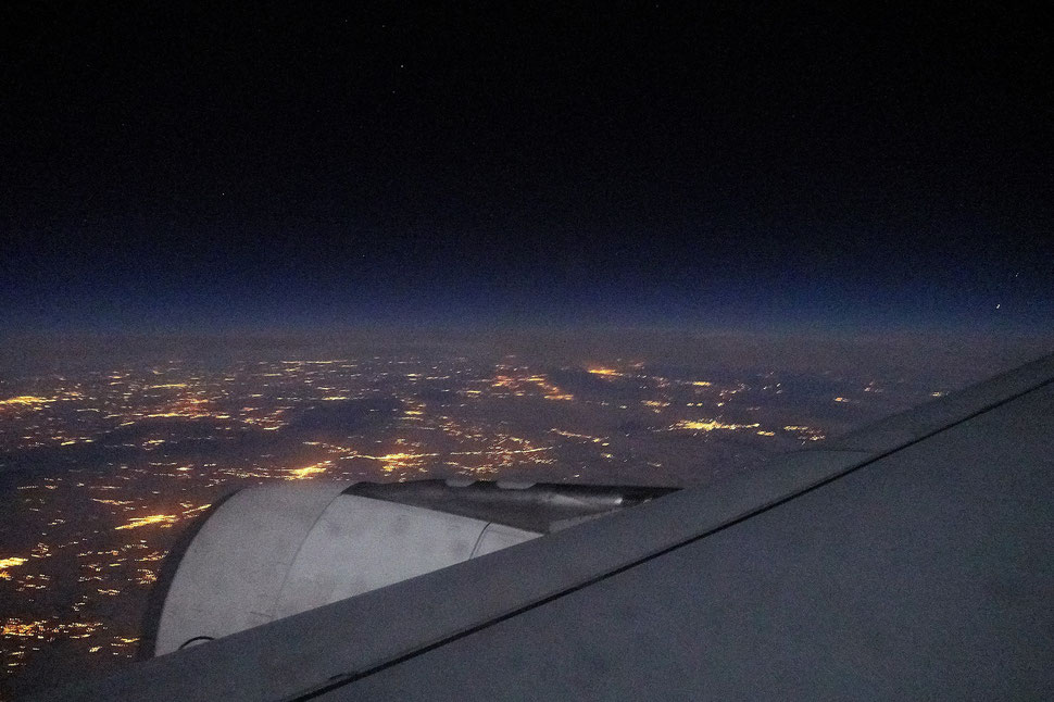 The image shows a night photograph through the window of an airplane; part of the wing, the lights of civilization and the dark sky are visible.