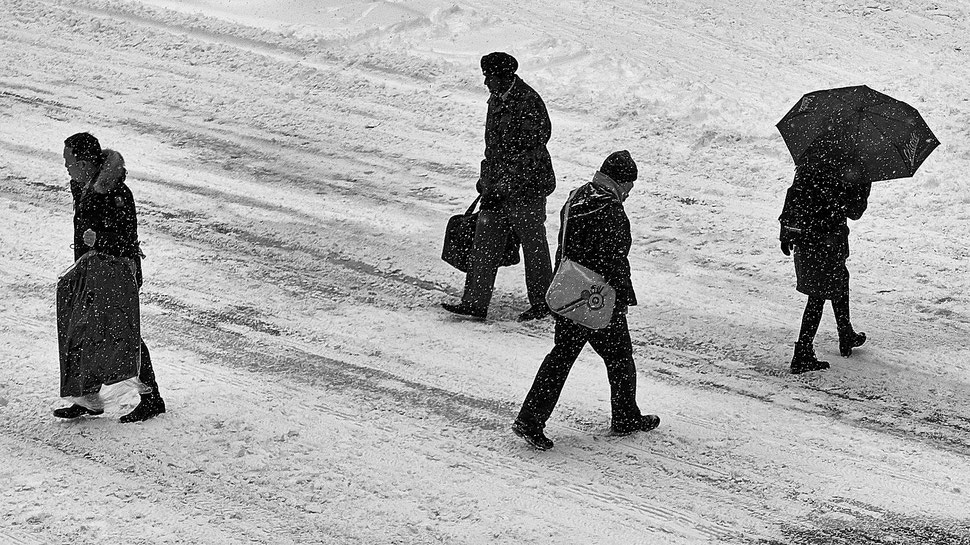 The image shows the black and white photograph of four people crossing a street during a snowstorm.