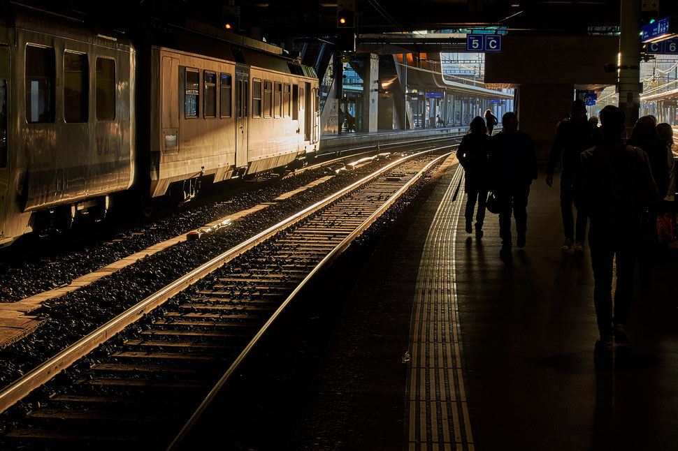 The image shows a photograph of platform 5 with some people in Bern's main train station. The evening sun shines on the tracks