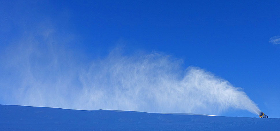 The image shows the photograph of a snow cannon blasting out snow against a blue sky.