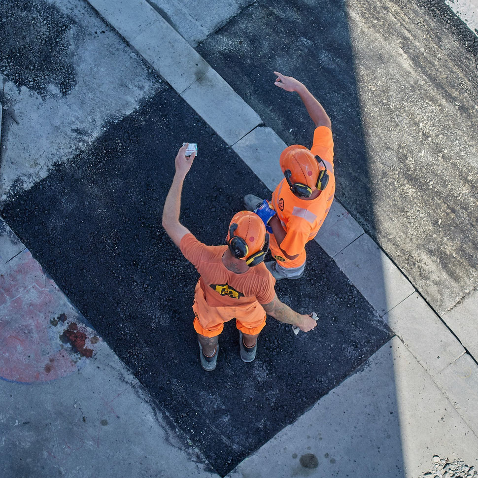 The image shows the aerial photograph of two construction workers with helmets who are gesturing.