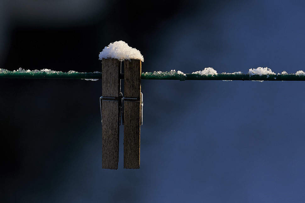 The image shows the photograph of two snow covered wooden clothespins on a clothesline against a dark background.