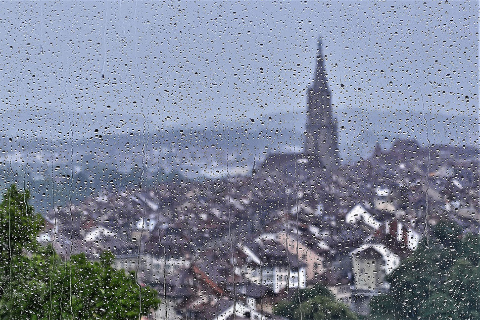 The image shows the blurred photograph of the old town of Bern through a window stained with raindrops.