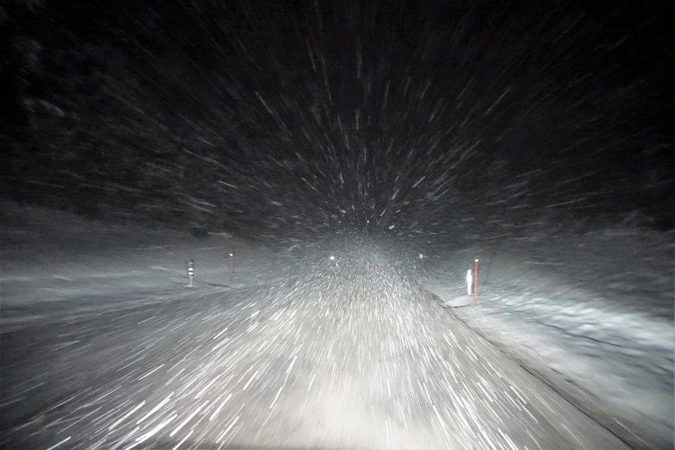 The image shows the night photograph of a snow coverd street lit by the headlights of a car and whirling snow flakes.
