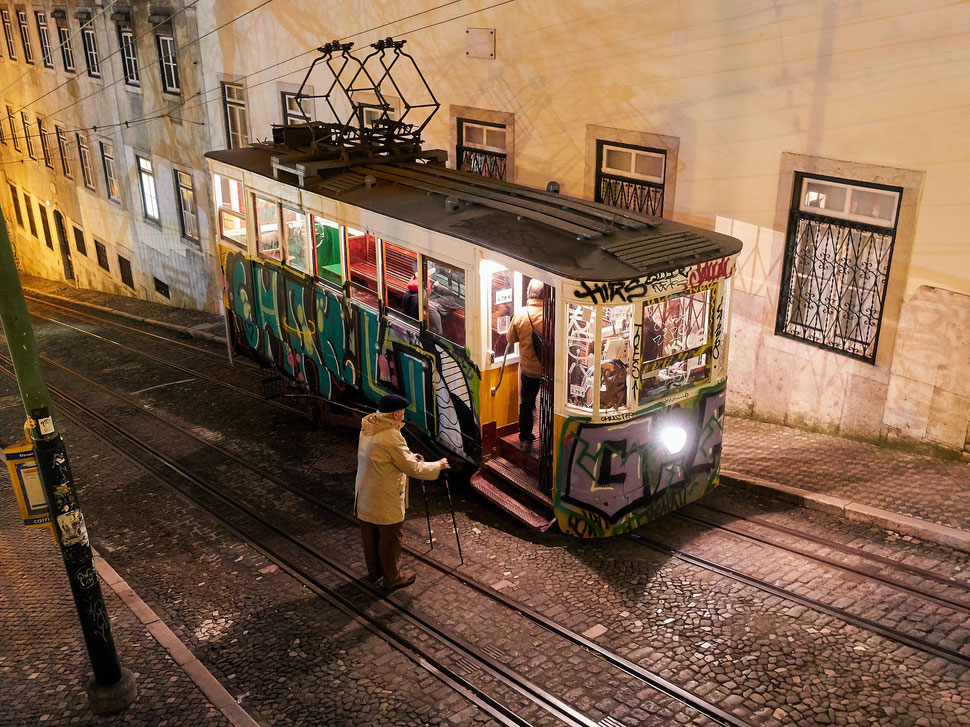 The image shows a photograph of an old man getting ready to enter a Tram (Ascensor da Gloria) in Lisbon. It is night an the street is lit by street lights.