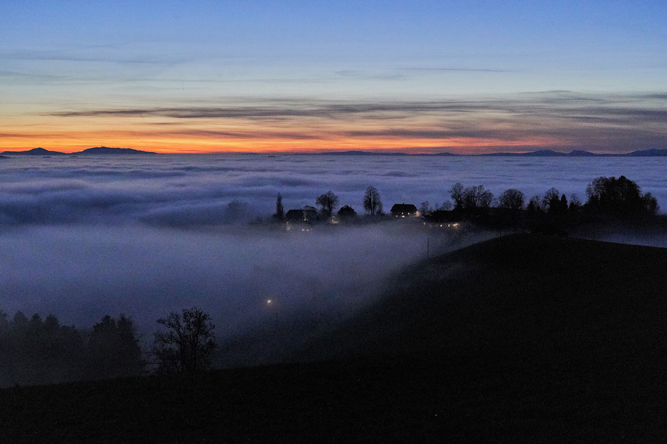 The image shows an evening photograph of a landscape with a sea of fog, some houses with lights, some trees and a colorful horizon.