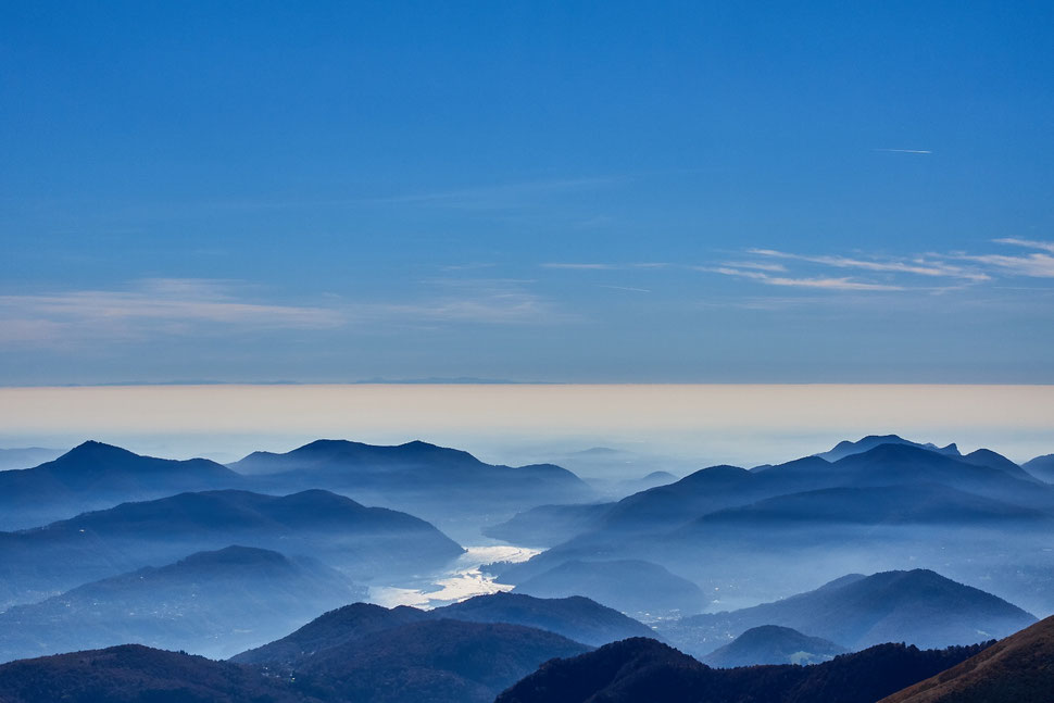 The imag shows the photograph of a landscape with a lake and mountains drenched in mist below a deep horizon and blue skies.
