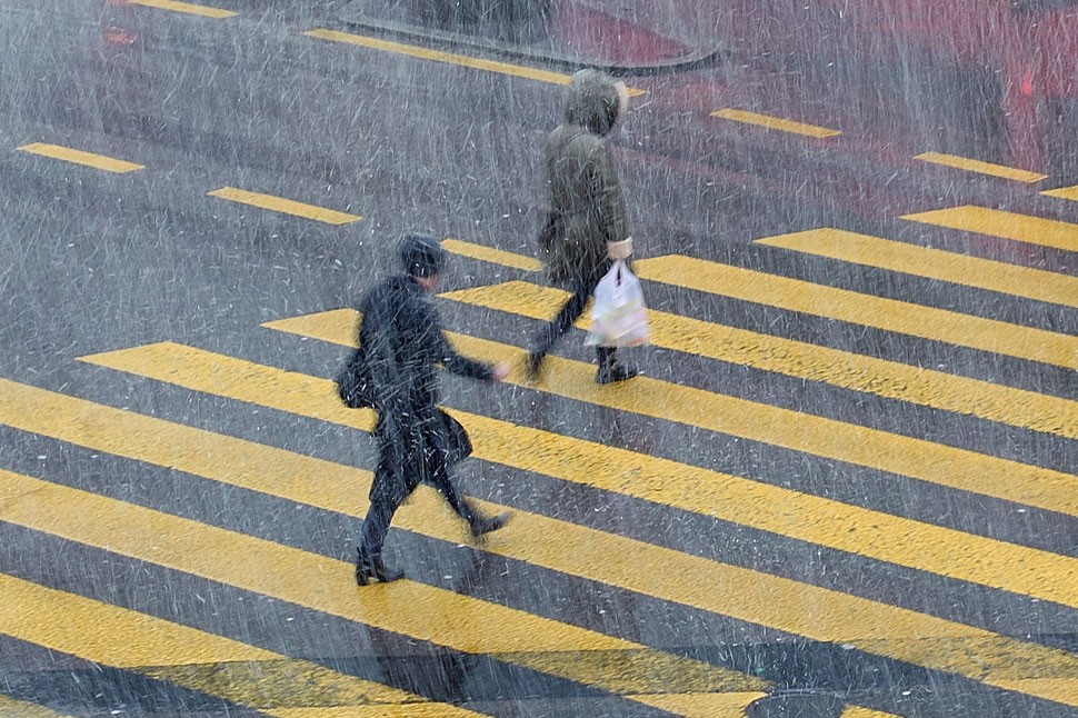 The image shows a photography of two women crossing a street in a snowstorm.