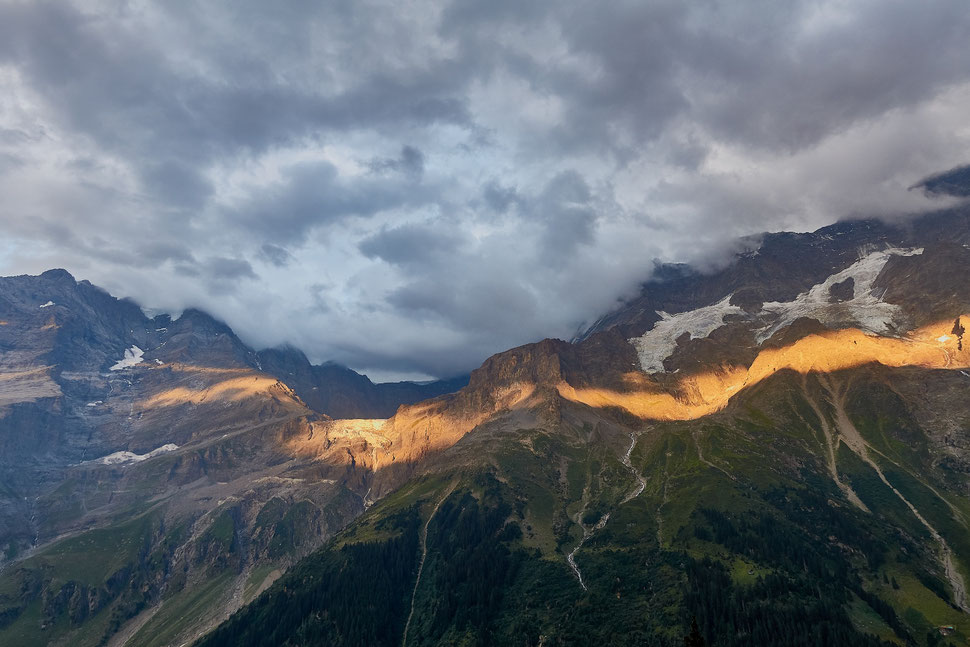 The image shows the photograph of mountains in the Bernese Oberland touched by a streak of evening sunlight under a clouded sky.