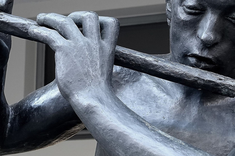 The photograph shows an image of a close-up of a statue playing the flute. Bild von Bern.
