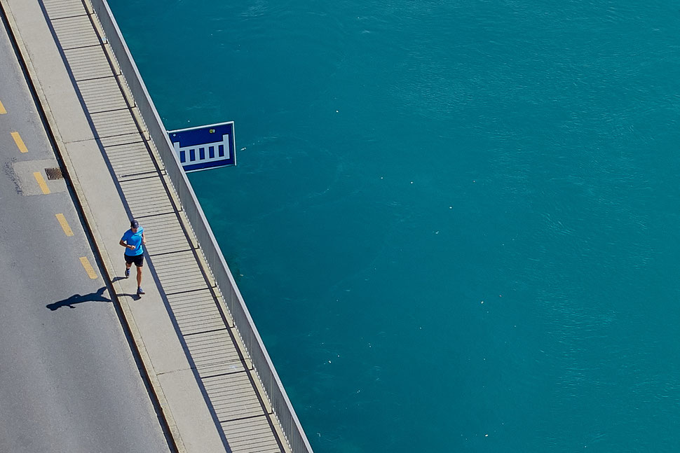 The image shows an aerial photograph of a man joggjng next to the Aare river in Bern.