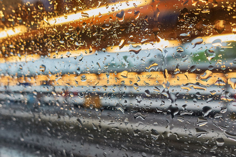The image shows the abstract photograph of a train window with rain drops and streaks of light.