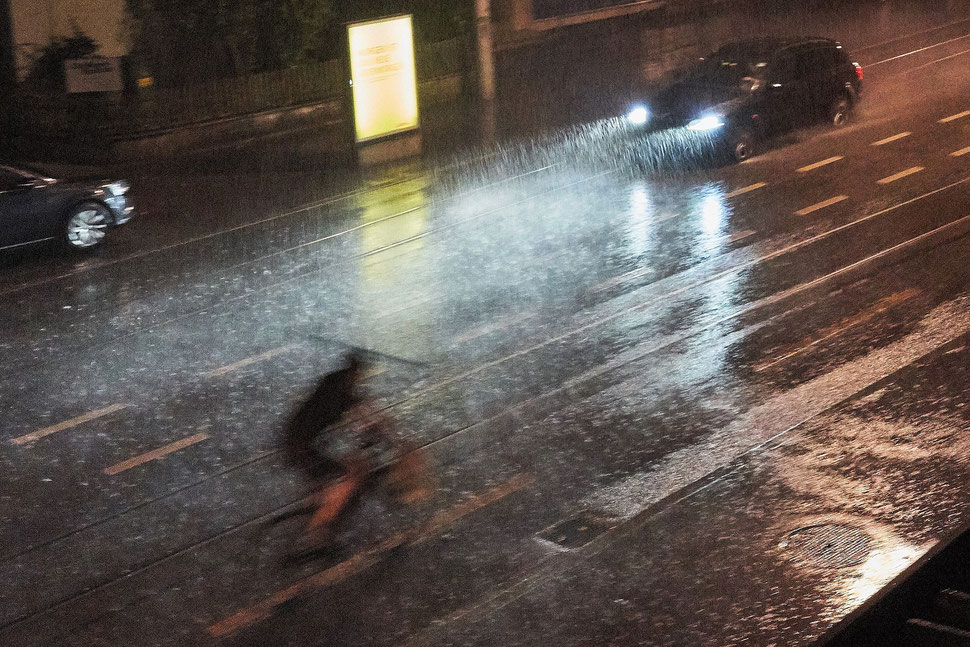 The image shows the photograph of a cyclist riding through a rain storm in the night.