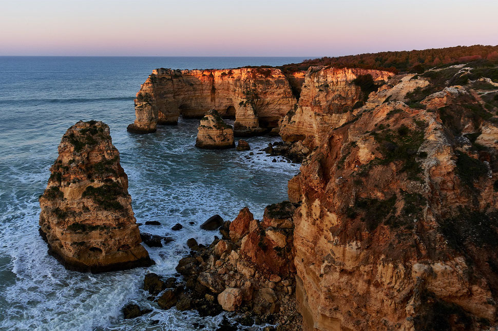 The image shows a photograph of faint sunlight on cliffs of the coast of the Algarve (Portugal).