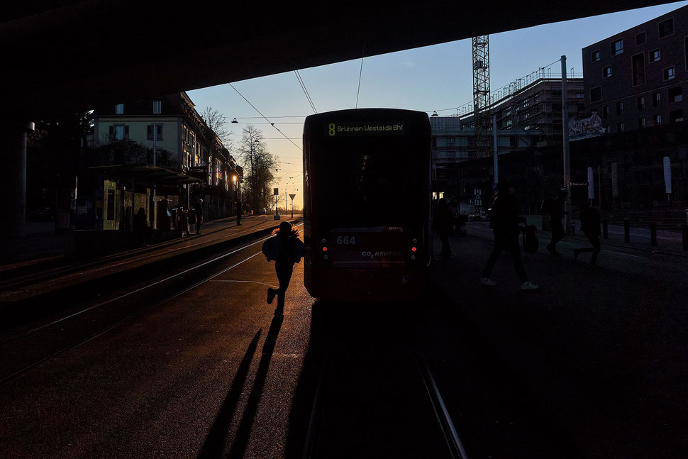 The image shows the photograph of a sand beach with rows of folded parasols.