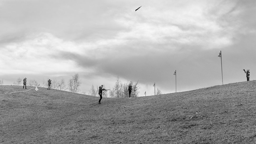 The image shows the black and white photograph of a man and four children flying kites on a cloudy afternoon in Winter.