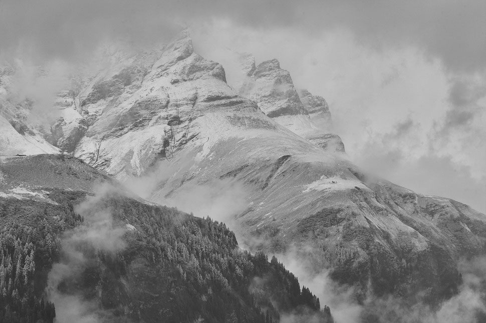 The image shows a black and white photograph of mountains that are partly hidden behind fog and lightly covered in snow.