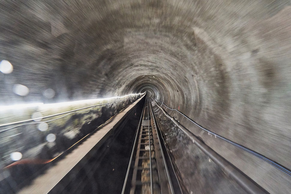 The image shows a photograph of a tunnel and tracks; the photo was taken through the rear window of a fast moving train.