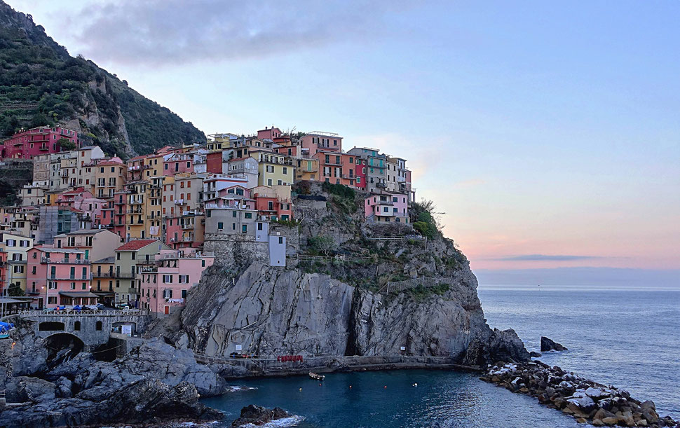 The image shows the photograph of the Italian village Manarola, which is built on rocks on the coast of the sea.